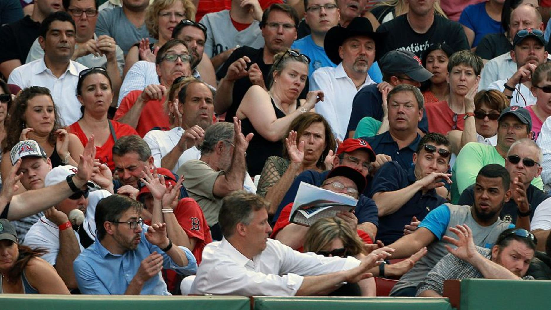 BOSTON - JUNE 17: Fans along the third base line duck for cover as a foul ball screams at them. The Boston Red Sox hosted the Minnesota Twins in a regular season MLB game at Fenway Park. (Photo by Jim Davis/The Boston Globe via Getty Images)