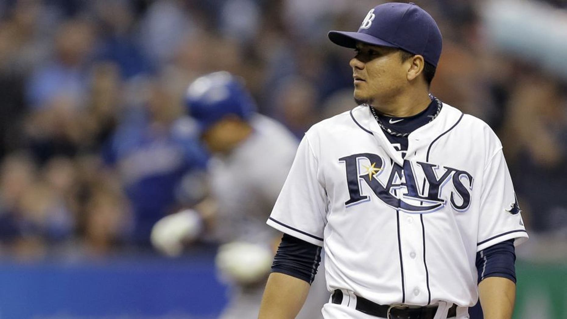 Tampa Bay Rays starting pitcher Erasmo Ramirez, foreground, looks at the home plate umpire as Kansas City Royals' Kendrys Morales runs the bases after hitting a two-run home run during the third inning of a baseball game Friday, Aug. 28, 2015, in St. Petersburg, Fla. (AP Photo/Chris O'Meara)