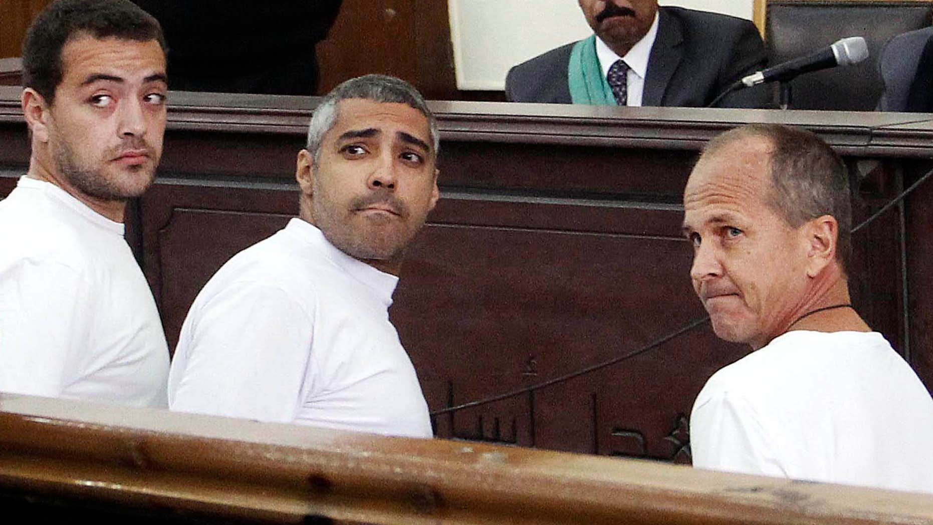 March 31, 2014:  Al-Jazeera English producer Baher Mohamed, left, Canadian-Egyptian acting Cairo bureau chief Mohammed Fahmy, center, and correspondent Peter Greste, right, appear in court along with several other defendants during their trial on terror charges, in Cairo.