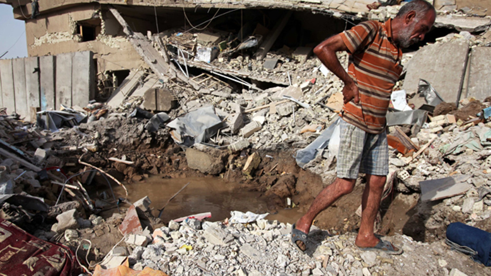 Aug. 26: An Iraqi man surveys the ruins of a collapsed building the day after a bombing in Baghdad, Iraq.