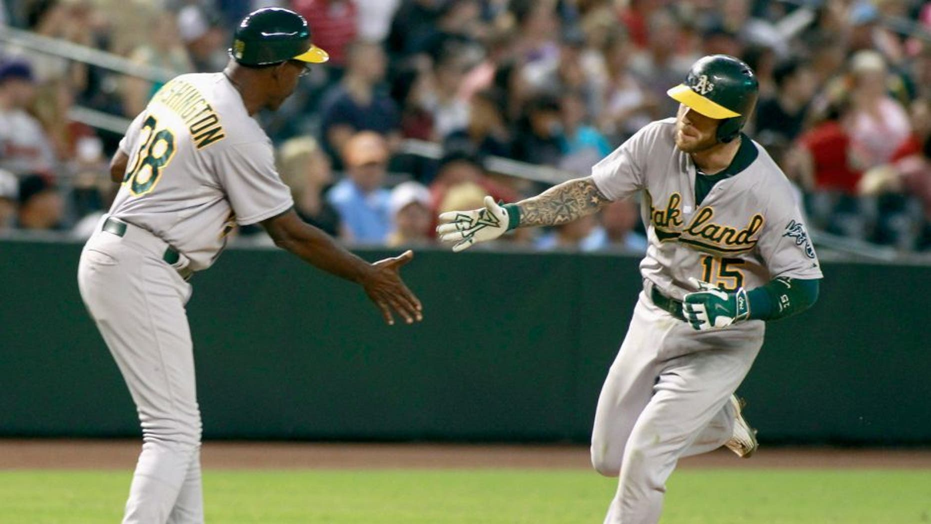 PHOENIX, AZ - AUGUST 28: Brett Lawrie #15 of the Oakland Athletics is congratulated by third base coach Ron Washington #38 after hitting a two-run home run against the Arizona Diamondbacks during the ninth inning of a MLB game at Chase Field on August 28, 2015 in Phoenix, Arizona. (Photo by Ralph Freso/Getty Images)