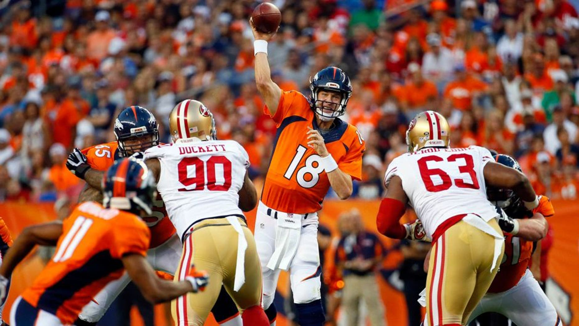 Denver Broncos quarterback Peyton Manning (18) throws as San Francisco 49ers defensive tackle Darnell Dockett (90) and Tony Jerod-Eddie (63) rush during the first half of an NFL preseason football game, Saturday, Aug. 29, 2015, in Denver. (AP Photo/Jack Dempsey)