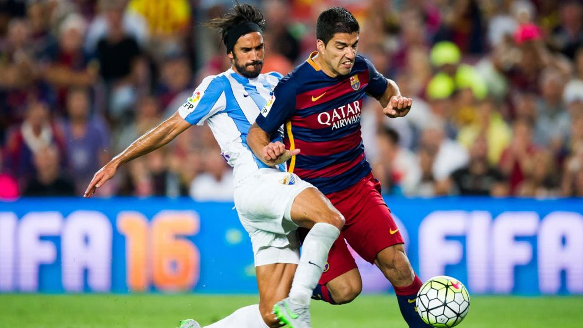 BARCELONA, SPAIN - AUGUST 29: Luis Suarez of FC Barcelona is brought down by Marcos Angeleri of Malaga CF during the La Liga match between FC Barcelona and Malaga CF at Camp Nou on August 29, 2015 in Barcelona, Spain. (Photo by Alex Caparros/Getty Images)