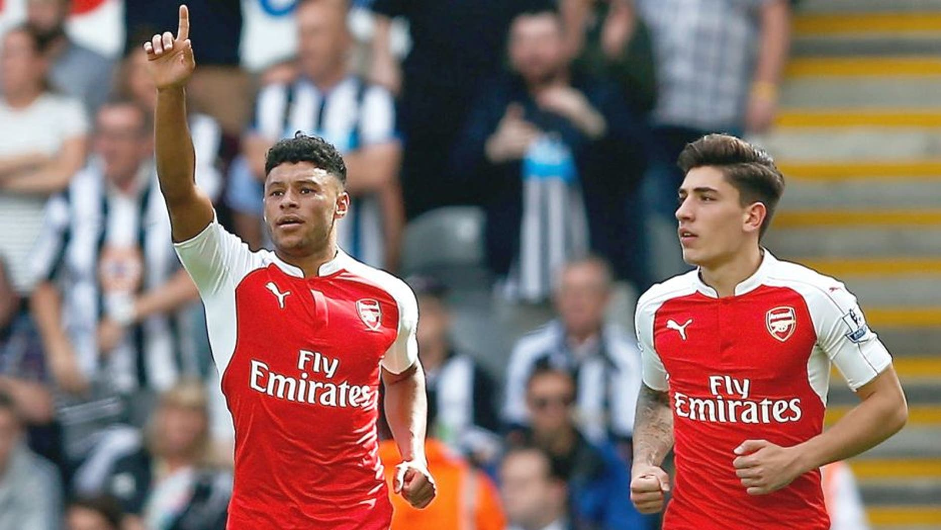 NEWCASTLE UPON TYNE, ENGLAND - AUGUST 29: Alex Oxlade-Chamberlain (L) of Arsenal celebrates his team's first goal, own goal by Fabricio Coloccini of Newcastle United during the Barclays Premier League match between Newcastle United and Arsenal at St James' Park on August 29, 2015 in Newcastle upon Tyne, England. (Photo by Dean Mouhtaropoulos/Getty Images)