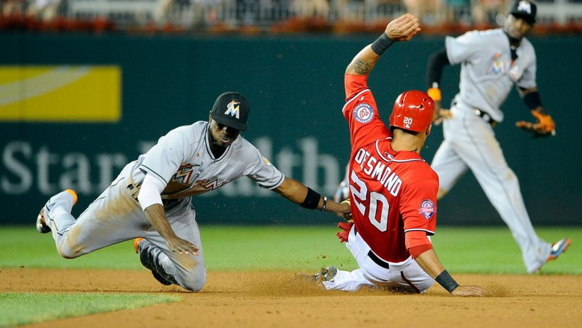 Aug 29, 2015; Washington, DC, USA; Miami Marlins second baseman Dee Gordon (9) tags out Washington Nationals shortstop Ian Desmond (20) attempting to steal second base during the fourth inning at Nationals Park. Mandatory Credit: Brad Mills-USA TODAY Sports