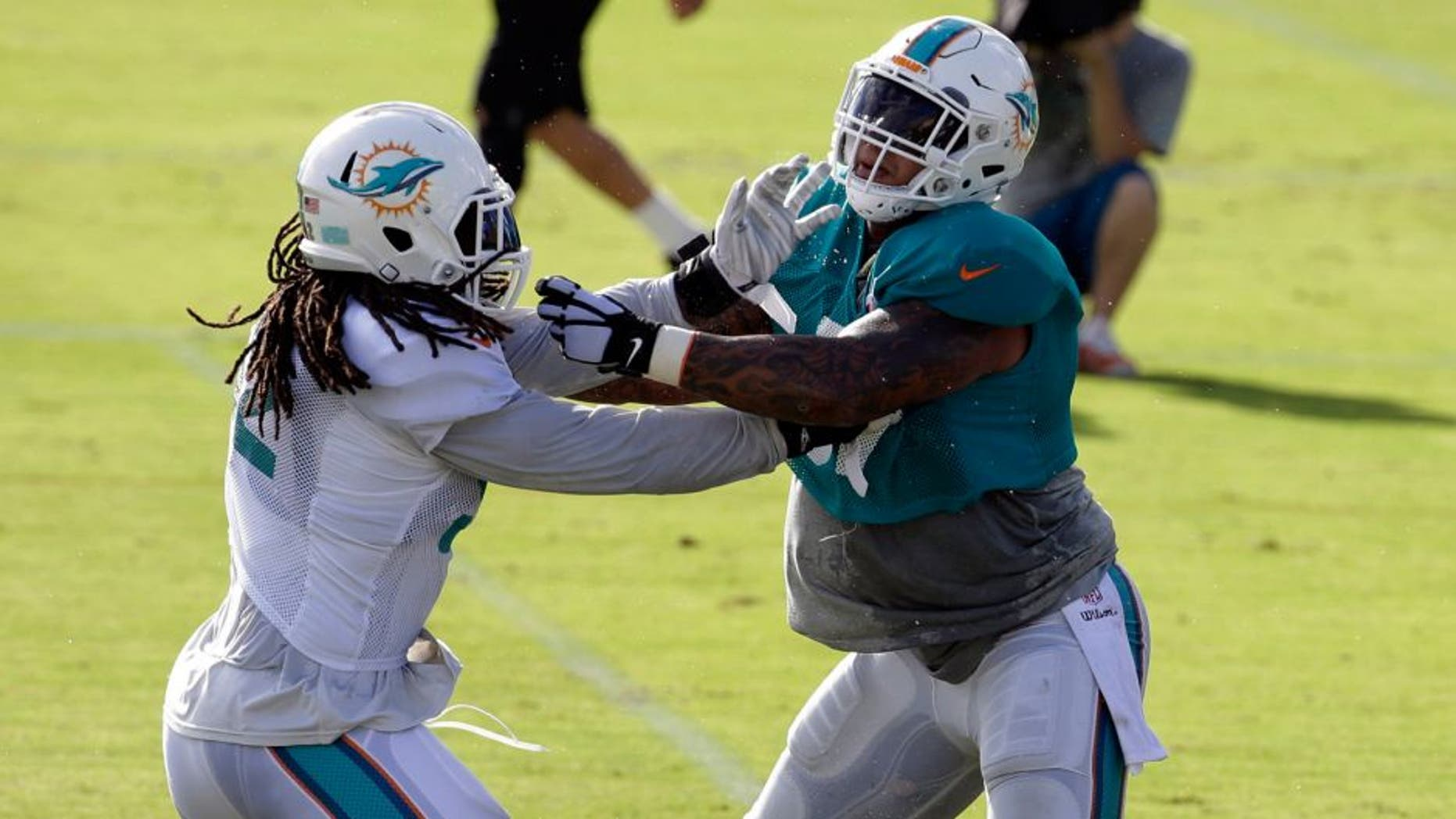 Miami Dolphins center Mike Pouncey, right, and linebacker Kelvin Sheppard, left, do drills during an NFL football training camp practice, Sunday, Aug. 16, 2015, in Davie, Fla. (AP Photo/Lynne Sladky)