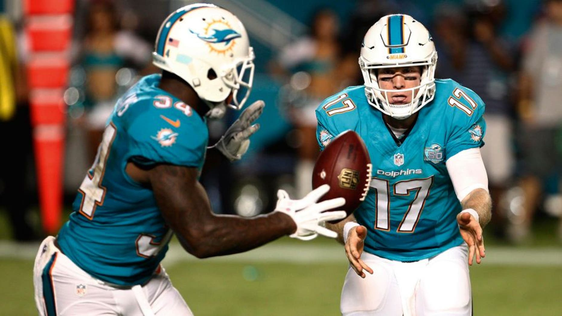 Aug 29, 2015; Miami Gardens, FL, USA; Miami Dolphins quarterback Ryan Tannehill (17) pitches to Dolphins running back Damien Williams (34) during the second quarter of an NFL preseason football game against the Atlanta Falcons at Sun Life Stadium. Mandatory Credit: Reinhold Matay-USA TODAY Sports