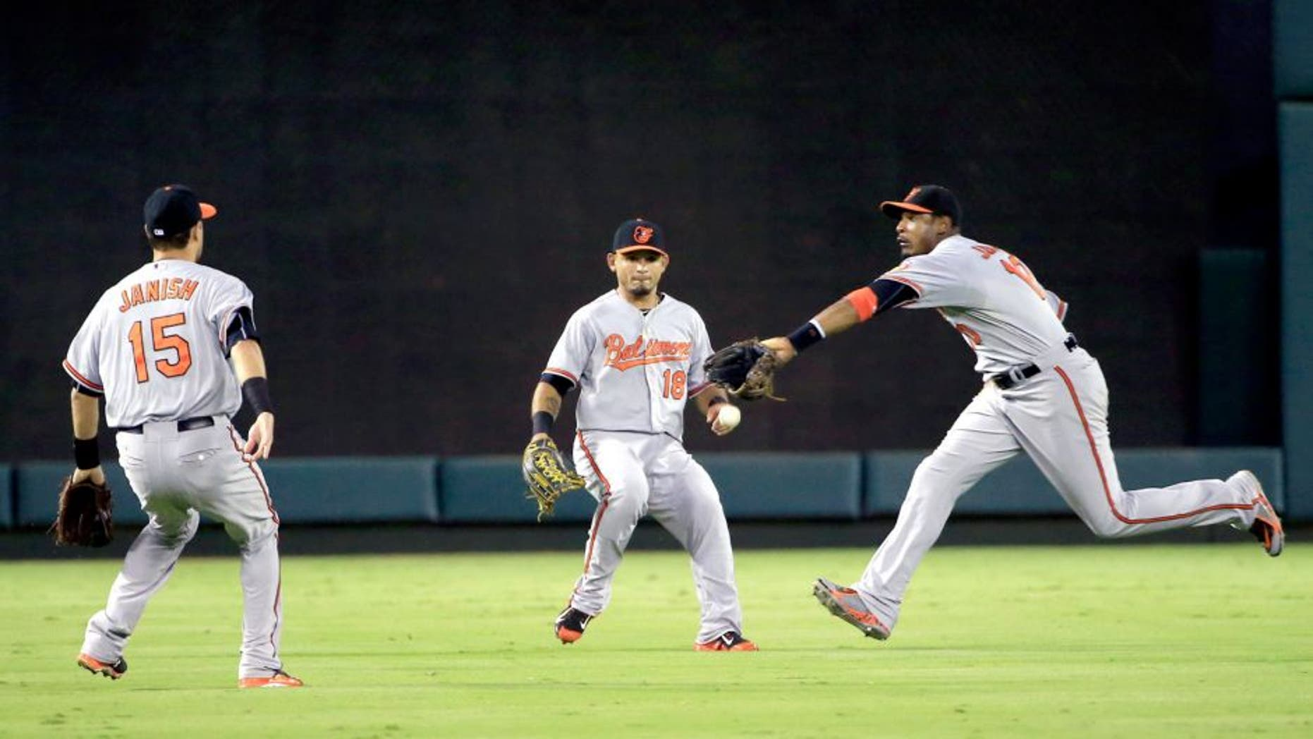 Aug 29, 2015; Arlington, TX, USA; Baltimore Orioles center fielder Adam Jones (10) and left fielder Gerardo Parra (18) and shortstop Paul Janish (15) cannot catch a fly ball during the fourth inning against the Texas Rangers at Globe Life Park in Arlington. Mandatory Credit: Kevin Jairaj-USA TODAY Sports