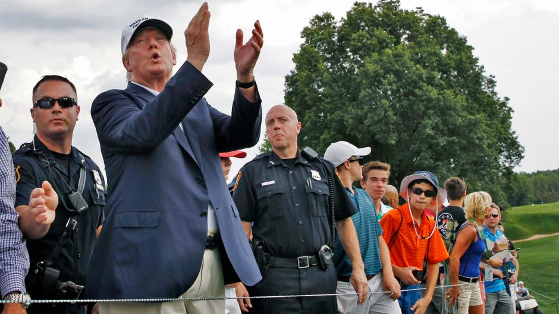 Republican presidential candidate Donald Trump, second left, applauds play as he walks with a crowd during the final round of play at The Barclays golf tournament Sunday, Aug. 30, 2015, in Edison, N.J. (AP Photo/Mel Evans)