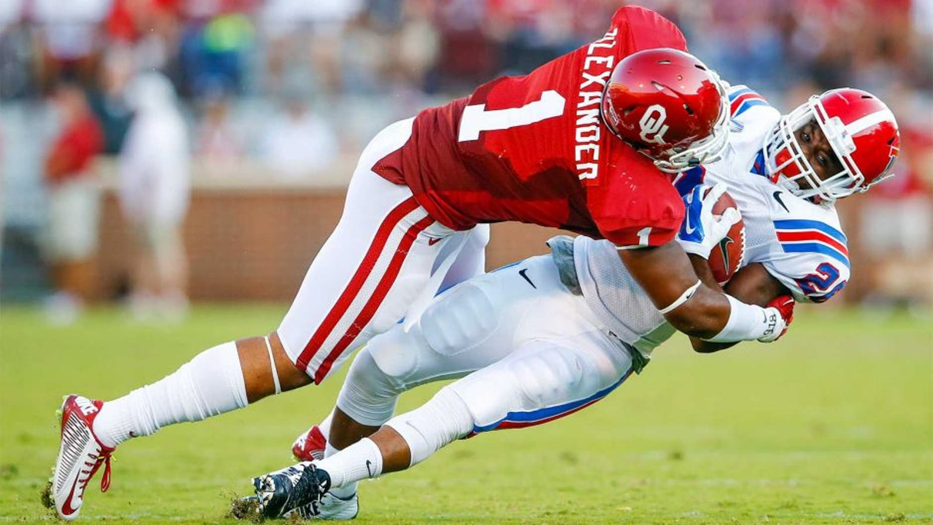 Aug 30, 2014; Norman, OK, USA; Oklahoma Sooners linebacker Dominique Alexander (1) tackles Louisiana Tech Bulldogs running back Kenneth Dixon (28) during the first half at Gaylord Family - Oklahoma Memorial Stadium. Mandatory Credit: Kevin Jairaj-USA TODAY Sports