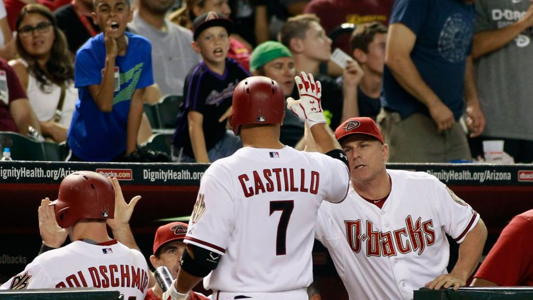 PHOENIX, AZ - AUGUST 28: Welington Castillo #7 of the Arizona Diamondbacks is congratulated by manager Chip Hale #3 (R) after hitting a sacrifice fly against the Oakland Athletics to score Paul Goldschmidt #44 (L) during the sixth inning of a MLB game at Chase Field on August 28, 2015 in Phoenix, Arizona. The Diamondbacks defeated the Athletics 6-4. (Photo by Ralph Freso/Getty Images)