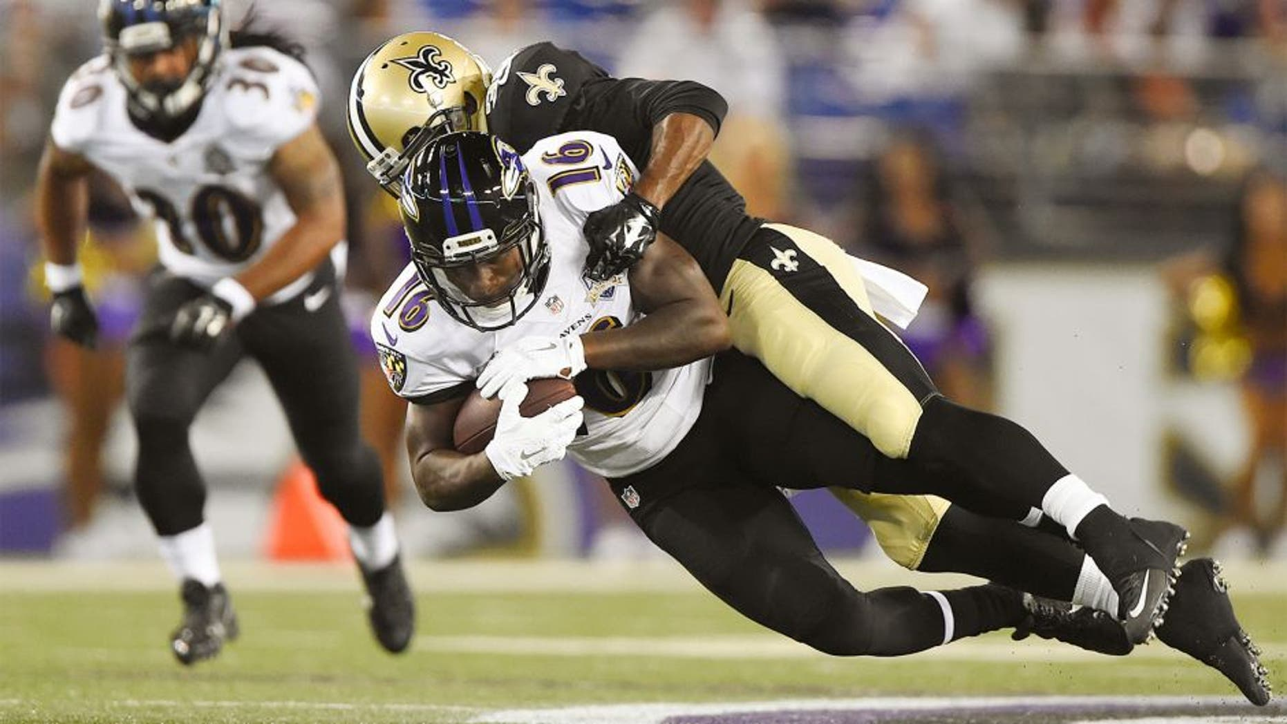 Aug 13, 2015; Baltimore, MD, USA; New Orleans Saints cornerback Damian Swann (38) tackles Baltimore Ravens wide receiver DeAndre Carter (16) during the fourth quarter in a preseason NFL football game at M&T Bank Stadium. Baltimore Ravens defeated New Orleans Saints 30-27. Mandatory Credit: Tommy Gilligan-USA TODAY Sports