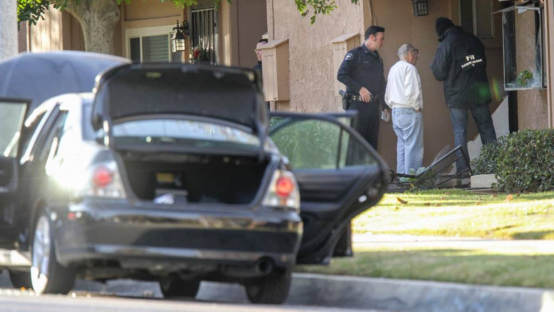 FBI agents interview a man, center, outside a home in connection to the shootings in San Bernardino, Thursday, Dec. 3, 2015, in Redlands, Calif. A heavily armed man and woman opened fire Wednesday on a holiday banquet for his co-workers, killing multiple people and seriously wounding others in a precision assault, authorities said. Hours later, they died in a shootout with police. (AP Photo/Ringo H.W. Chiu)