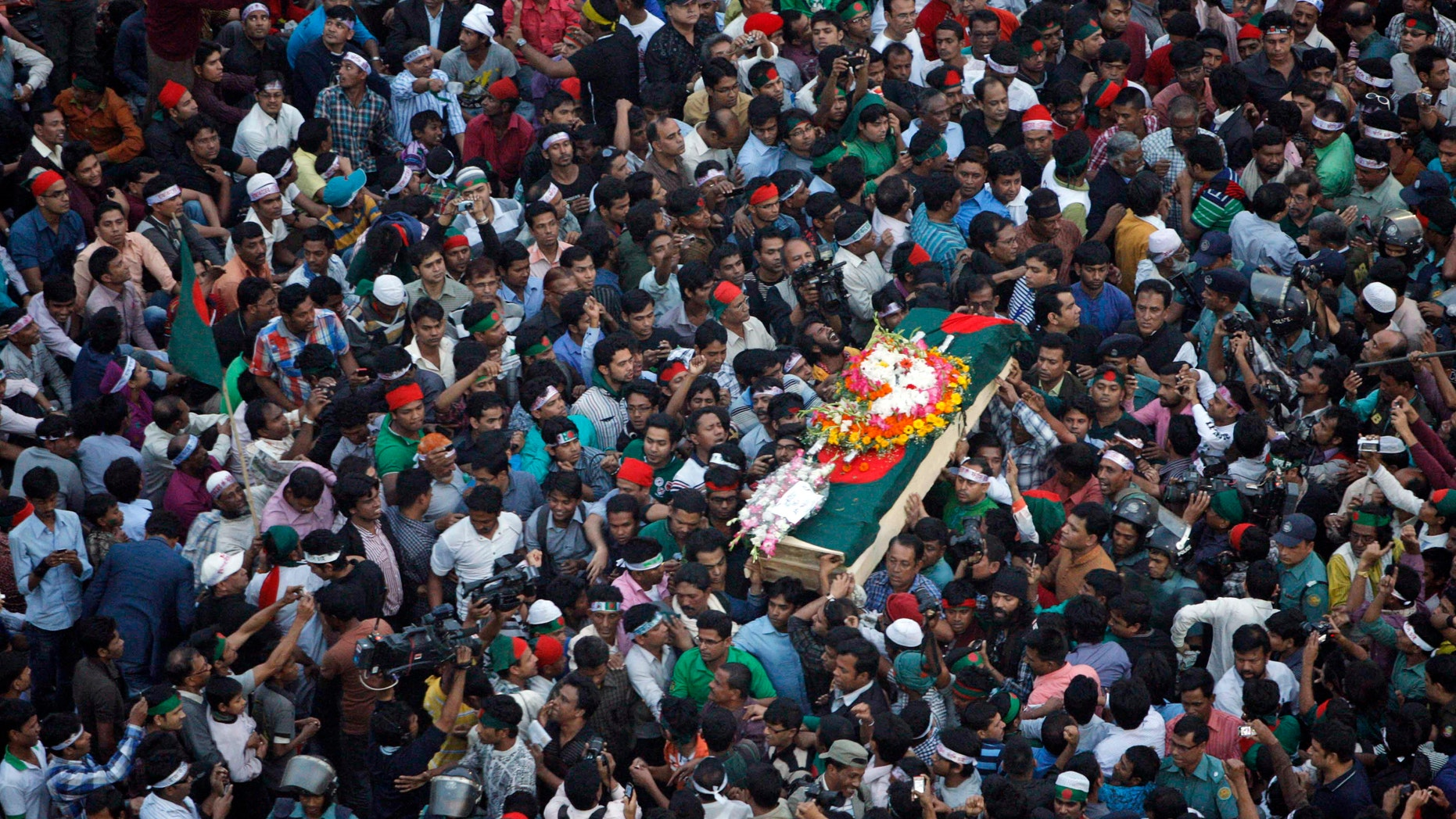 FILE - In this Feb. 16, 2013 file photo, Bangladeshi mourners carry the coffin containing the body of blogger Rajib Haider for funeral in Dhaka, Bangladesh. Haider had been critical of the Islamic group Jamaat-e-Islami, whose leader Abdul Quader Mollah was recently given a life sentence for his role in the killing of 381 civilians during the nation's 1971 war for independence from Pakistan. On Sunday, Feb. 17, 2013, Bangladesh parliament has amended the country's war crimes law that will allow the prosecution to appeal the life imprisonment of an opposition leader which it says has been lenient. (AP Photo/Pavel Rahman, File)