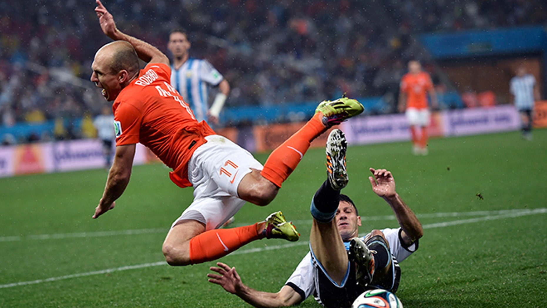 Netherlands' Arjen Robben goes down under a challenge from Argentina's Martin Demichelis during the World Cup semifinal soccer match between the Netherlands and Argentina at the Itaquerao Stadium in Sao Paulo Brazil, Wednesday, July 9, 2014. (AP Photo/Martin Meissner)