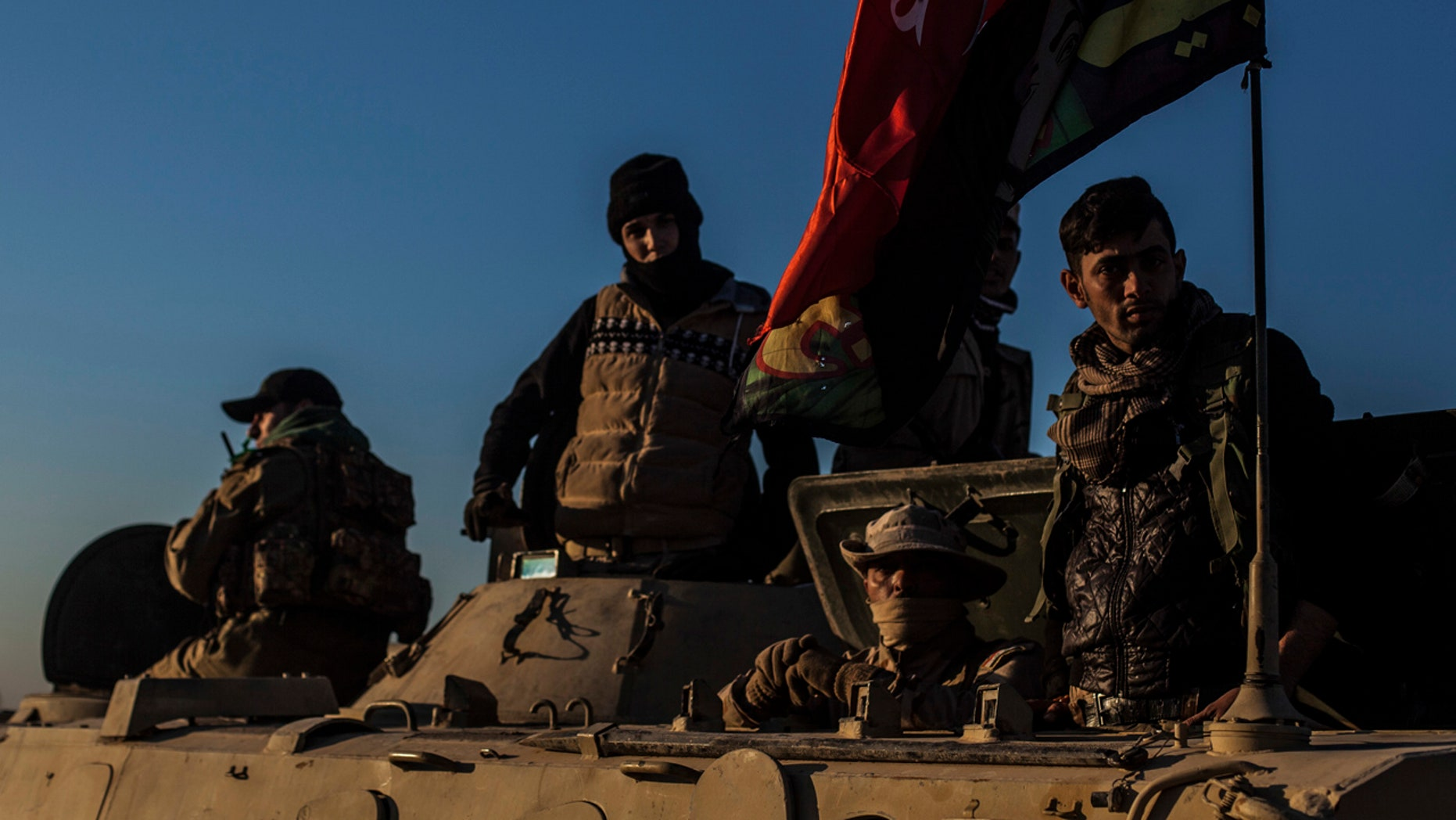 Iraqi Army soldiers are seen atop an armored vehicle while waiting to go to the frontline at the outskirts of Mosul in Al Intisa district, Mosul, Iraq, Tuesday, Dec. 6, 2016.