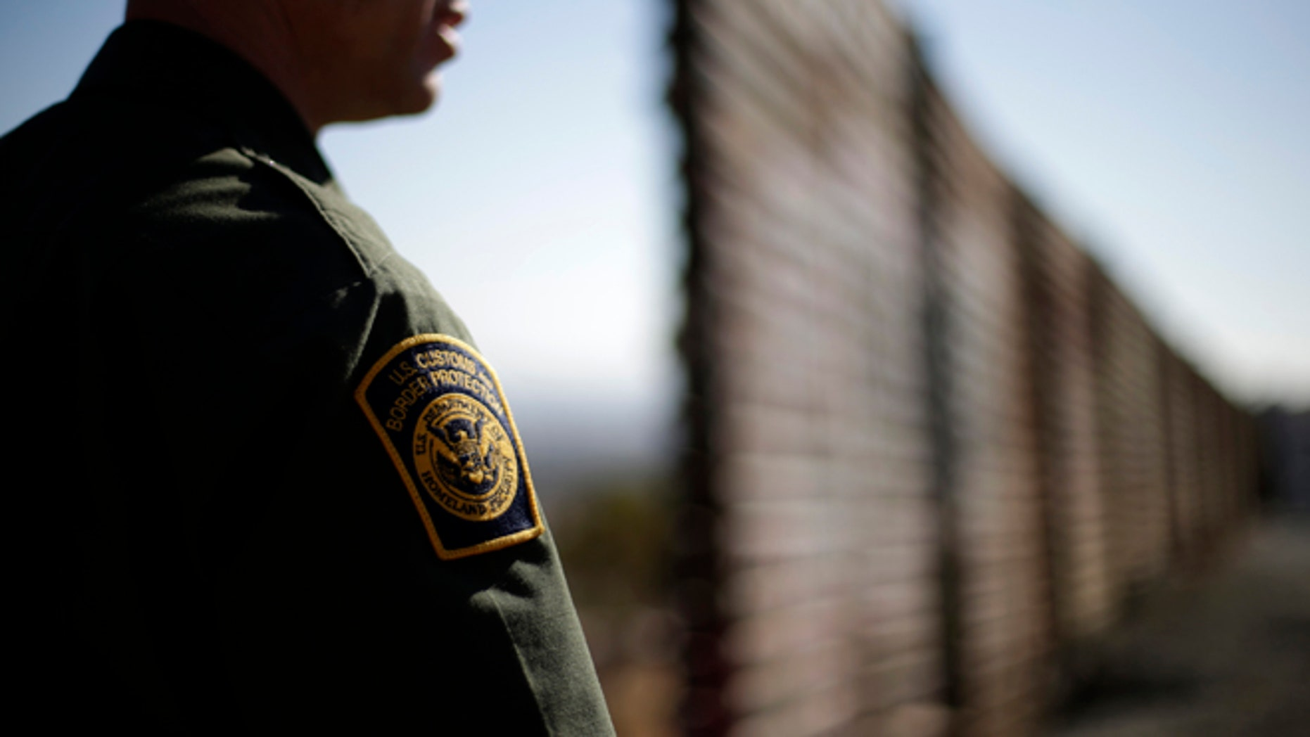 In this June 13, 2013 picture, U.S. Border Patrol agent Jerry Conlin looks to the north near where the border wall ends as is separates Tijuana, Mexico, left, and San Diego, right.  Illegal immigration into the United States would decrease by only 25 percent under a far-reaching Senate immigration bill, according to an analysis by the Congressional Budget Office that also finds the measure reduces federal deficits by billions. (AP Photo/Gregory Bull)