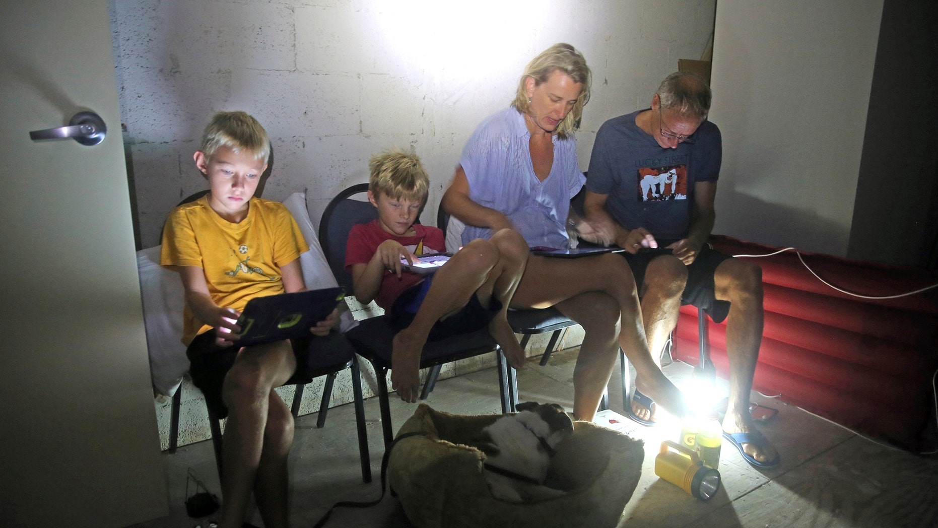 The Blinckman family use their personal devices while sheltering in a stairwell utility closet as Hurricane Irma goes over Key West, Fla., Sunday, Sept. 10, 2017. Hurricane Irma made landfall near Cudjoe Key as a Category 4 hurricane. (Charles Trainor Jr/The Miami Herald via AP)
