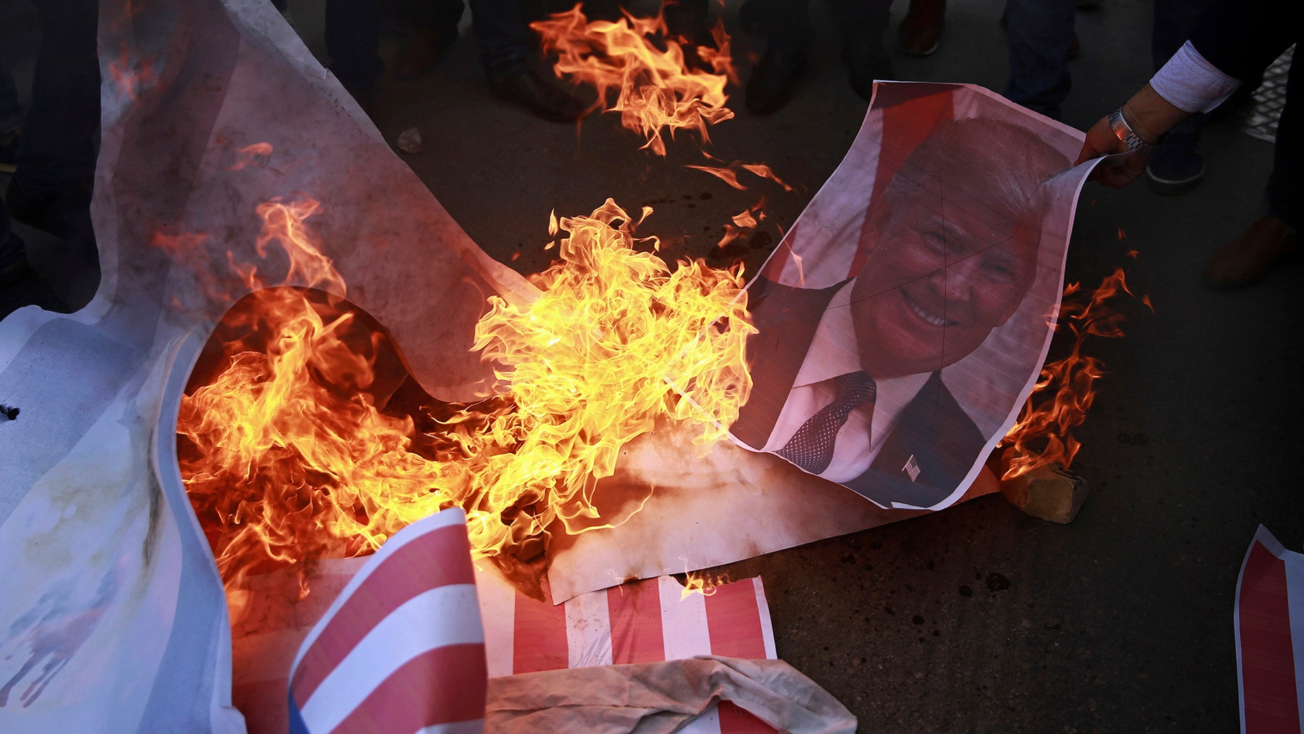 Palestinian protesters burn a poster of PresidentTrump and a representation of an American flag earlier in December.