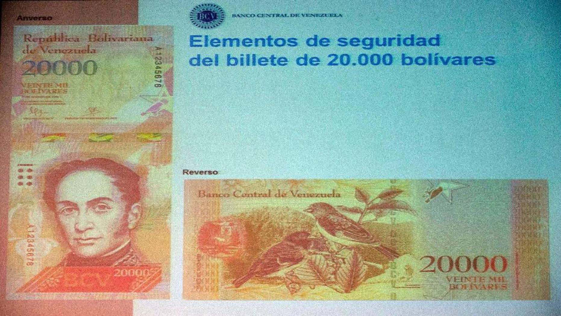 The front and back of the newly issued 20,000 Bolivar is displayed during a news conference in Caracas, Venezuela, Wednesday, Dec. 7, 2016. Venezuelan Central Bank President Nelson Merentes unveiled the new series of higher-denominated bills as triple-digit inflation and a currency meltdown leave the country's largest note worth just around 2 U.S. cents on the black market. (AP Photo/Fernando Llano)