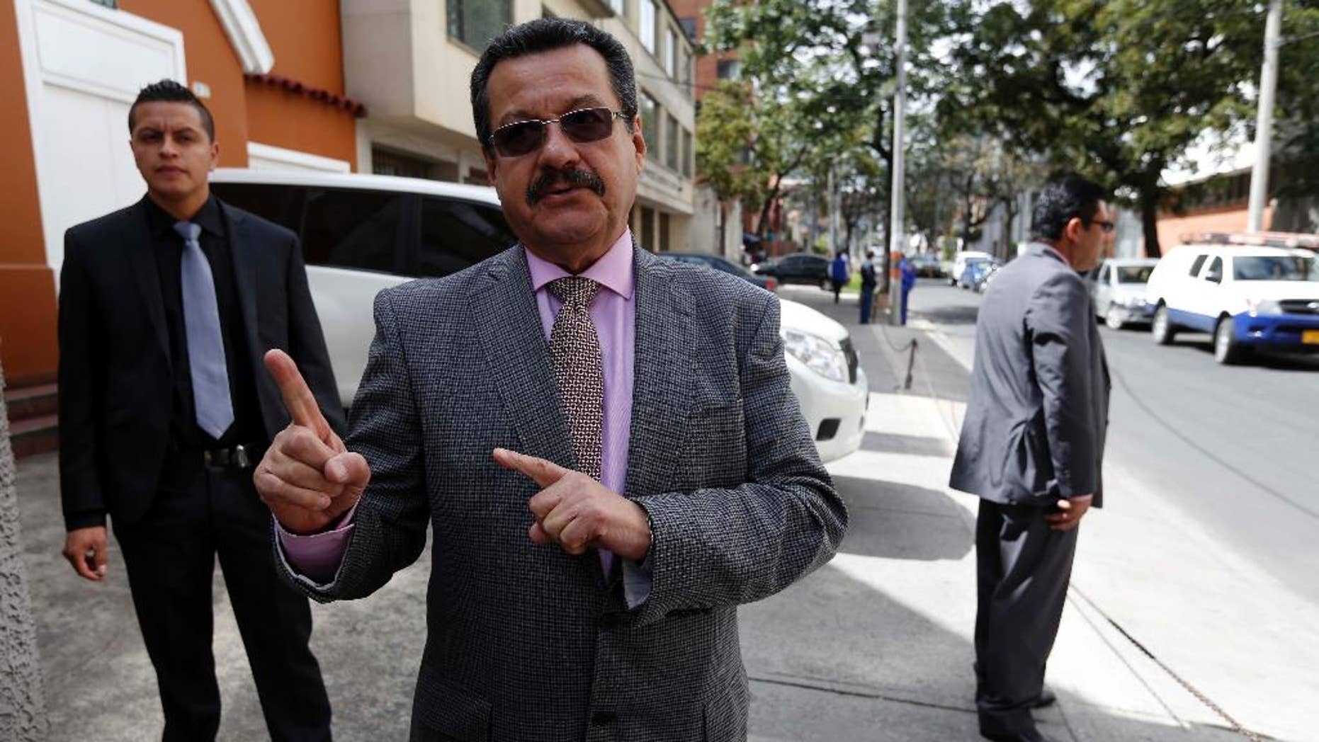 "In this Sept. 30, 2014 photo, Carlos Lozano, director of the Colombian Communist Party's weekly ""Voz,"" speaks to The Associated Press as two bodyguards watch over him, outside his office in Bogota, Colombia. Lozano, a Communist politician who has been an intermediary to the FARC, says the government isn't doing enough to convince the rebels they will be safer on the streets than they are on the battlefield. (AP Photo/Fernando Vergara)"