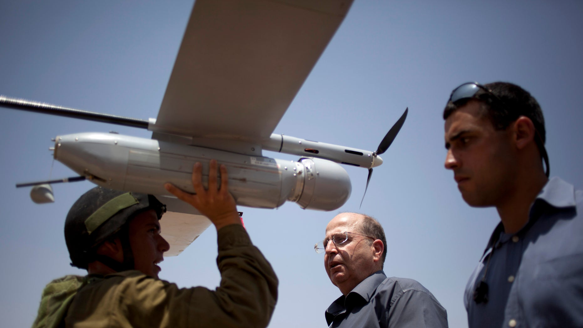 "File - In this July 9, 2013 file photo, an Israeli soldier holds up a Skylark I (Rochev Shamayim) unmanned drone as part of a demonstration for Israel's Defense Minister Moshe Yaalon, center, in an urban warfare army training facility, near Zeelim, southern Israel. Yaalon said Tuesday Dec. 3, 2013,  that Israel is transferring food, including baby food, as well as water and other ""basic needs"" to Syria. (AP Photo/Ariel Schalit, File)"