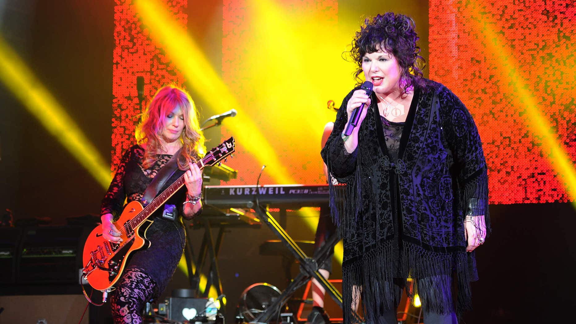 FILE - This June 17, 2013 file photo shows Nancy Wilson, left, and Ann Wilson of Heart performing on opening night of the Heartbreaker Tour at the Cruzan Amphitheater in West Palm Beach, Fla.