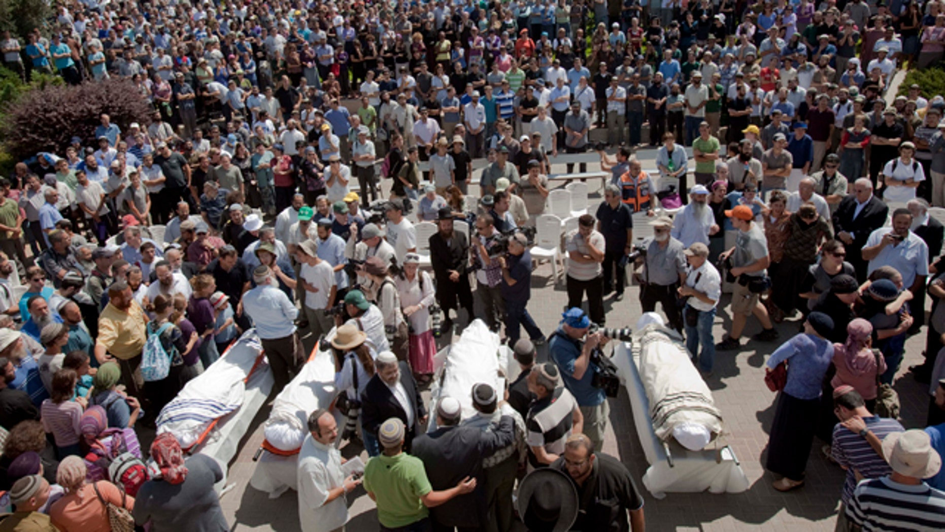 Sept. 1: Israeli mourners stand around the bodies of four people who were killed in a Palestinian shooting attack when they drove through the West Bank as a new round of Mideast talks opened in Washington.