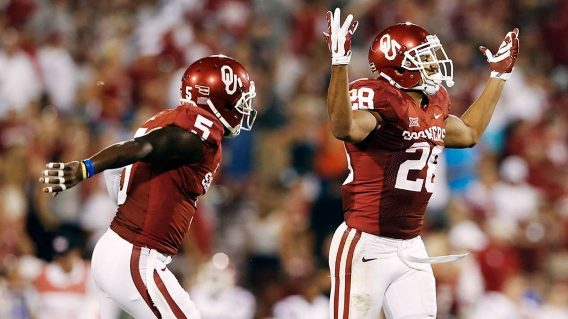 Aug 30, 2014; Norman, OK, USA; Oklahoma Sooners running back Alex Ross (28) celebrates with wide receiver Durron Neal (5) after returning a long punt during the game against the Louisiana Tech Bulldogs at Gaylord Family - Oklahoma Memorial Stadium. Mandatory Credit: Kevin Jairaj-USA TODAY Sports