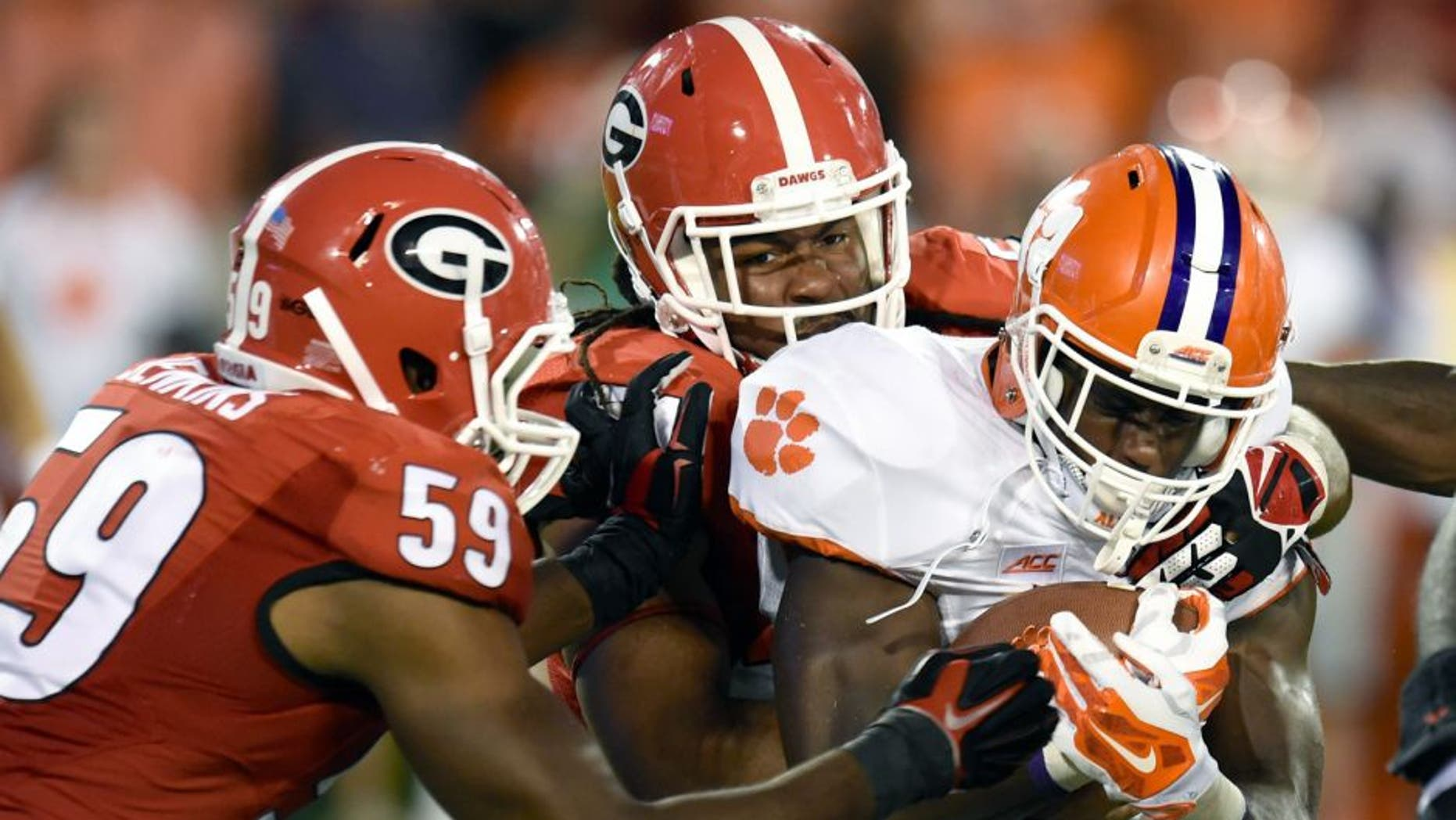 Aug 30, 2014; Athens, GA, USA; Clemson Tigers running back D.J. Howard (22) is tackled by Georgia Bulldogs linebacker Jordan Jenkins (59) and linebacker Ramik Wilson (51) during the second half at Sanford Stadium. Georgia defeated Clemson 45-21. Mandatory Credit: Dale Zanine-USA TODAY Sports