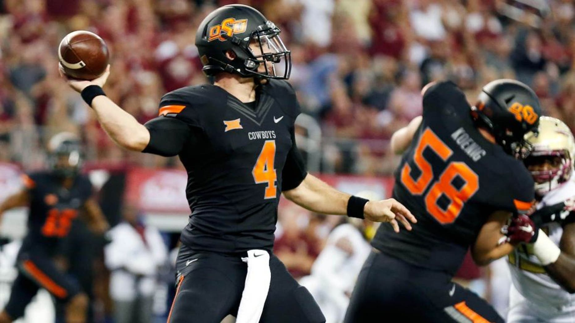 Aug 30, 2014; Arlington, TX, USA; Oklahoma State Cowboys quarterback J.W. Walsh (4) throws against the Florida State Seminoles during the first quarter at AT&T Stadium. Mandatory Credit: Matthew Emmons-USA TODAY Sports