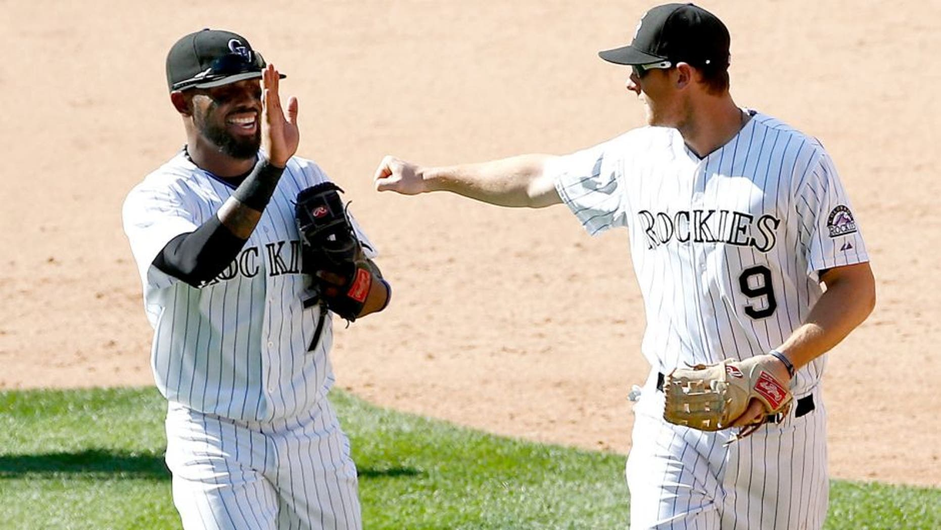 DENVER, CO - SEPTEMBER 01: Shortstop Jose Reyes #7 of the Colorado Rockies and second baseman DJ LeMahieu #9 of the Colorado Rockies celebrate after they teamed up with Ben Paulsen #10 of the Colorado Rockies for a triple play on a line drive by Paul Goldschmidt #44 of the Arizona Diamondbacks in the ninth inning at Coors Field on September 1, 2015 in Denver, Colorado. The Diamondbacks defeated the Rockies 6-4. (Photo by Doug Pensinger/Getty Images)