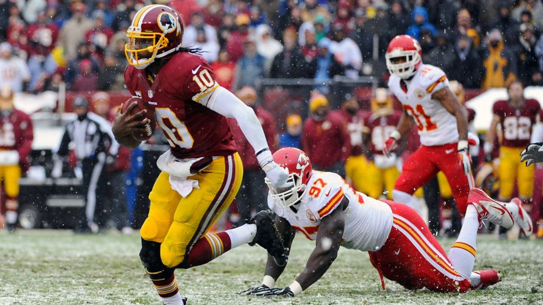 Dec 8, 2013; Landover, MD, USA; Washington Redskins quarterback Robert Griffin III (10) avoids the tackle by Kansas City Chiefs defensive end Allen Bailey (97) during the second quarter at FedEx Field. Mandatory Credit: Brad Mills-USA TODAY Sports