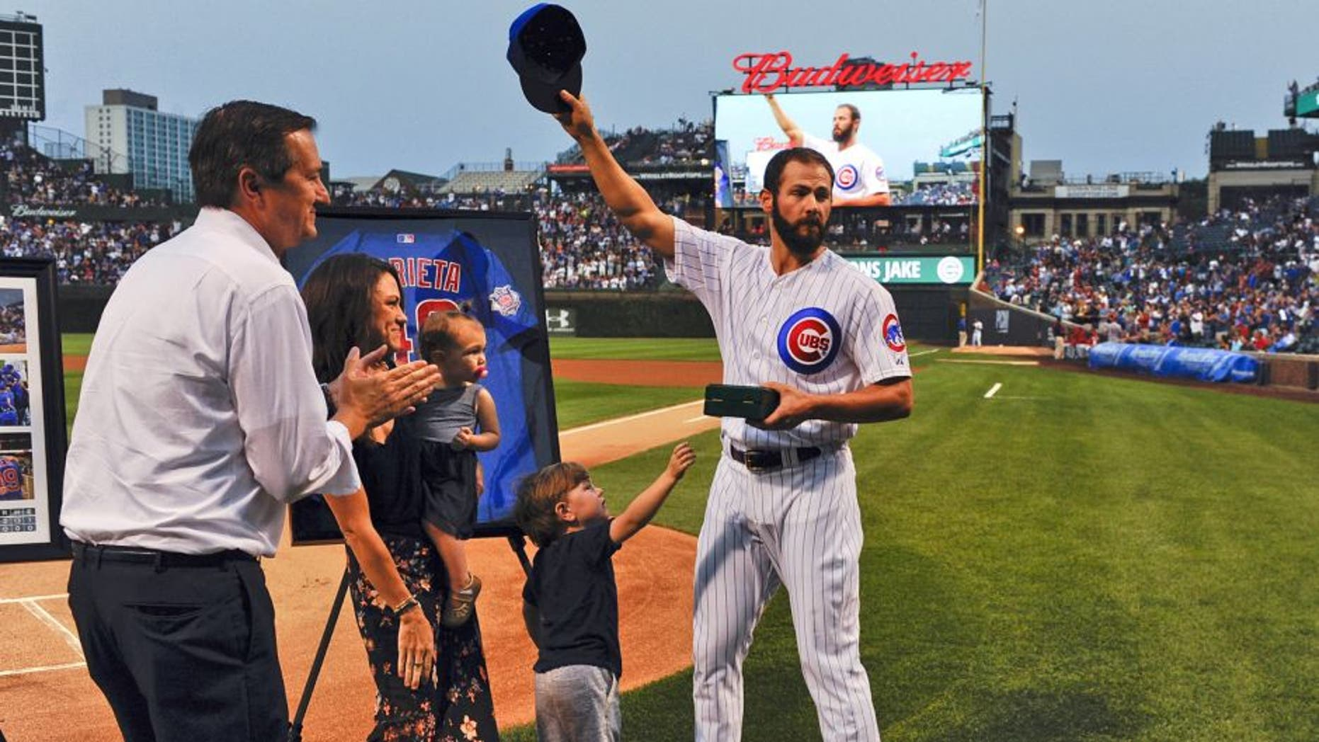 Aug 31, 2015; Chicago, IL, USA; Chicago Cubs starting pitcher Jake Arrieta (49), acknowledges the crowd while standing with his family, Cooper (son) and Palmer (daughter), Brittany Arrieta, his wife, and Chicago Cubs owner Tom Ricketts before the game against the Cincinnati Reds at Wrigley Field. Arrieta pitched a no-hitter the night before in Los Angeles. Mandatory Credit: Matt Marton-USA TODAY Sports
