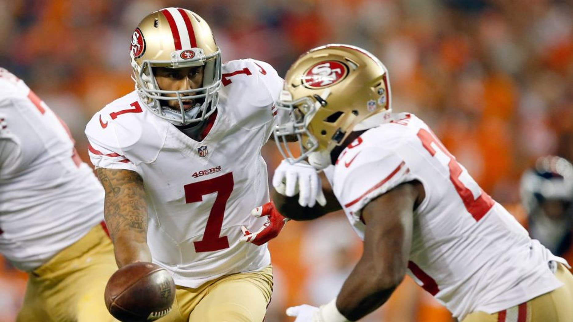 DENVER, CO - AUGUST 29: Quarterback Colin Kaepernick #7 of the San Francisco 49ers hands the ball off to running back Carlos Hyde #28 of the San Francisco 49ers against the Denver Broncos during preseason action at Sports Authority Field at Mile High on August 29, 2015 in Denver, Colorado. (Photo by Doug Pensinger/Getty Images)