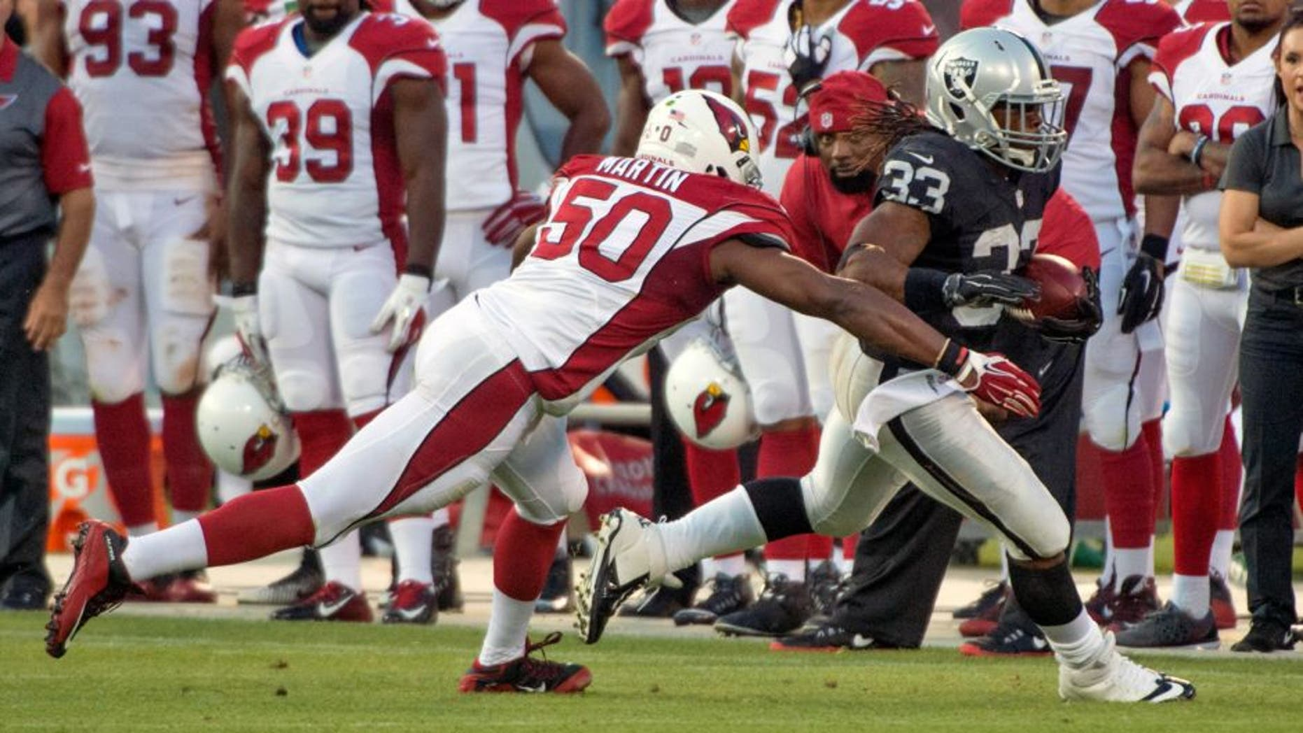 August 30, 2015; Oakland, CA, USA; Oakland Raiders running back Trent Richardson (33) runs with the ball against Arizona Cardinals linebacker Gabe Martin (50) during the third quarter in a preseason NFL football game at O.co Coliseum. The Cardinals defeated the Raiders 30-23. Mandatory Credit: Kyle Terada-USA TODAY Sports