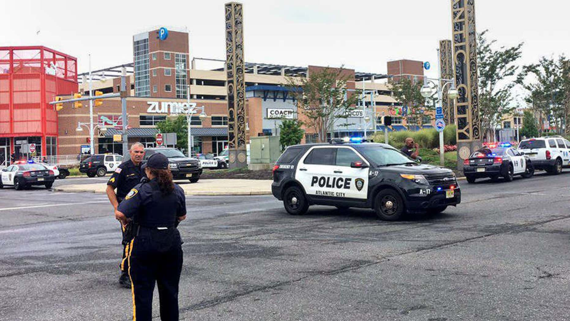 Sept. 1, 2016: Police officers block off a section of roadway adjacent to Tanger Outlets The Walk shopping center in Atlantic City, N.J., following a shooting incident.