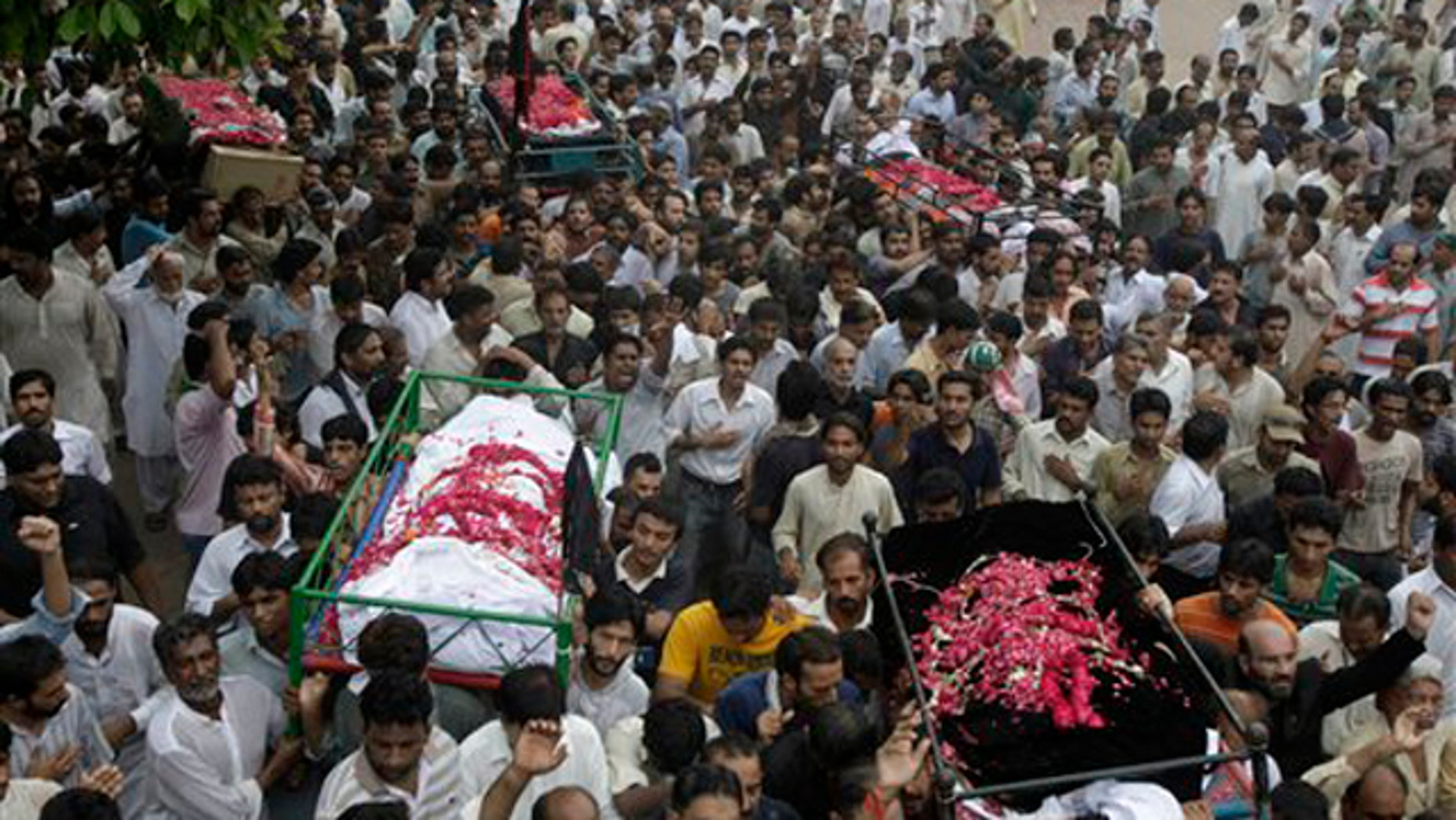 Sept. 2: Mourners carry the dead bodies of those killed in bomb blasts for burial in Lahore, Pakistan. Thousands of Shiite Muslims, thumping their chests and crying, mourned at funeral prayers for victims of the triple bombing that heaped more tragedy on Pakistan, which is already struggling to cope with devastating floods.