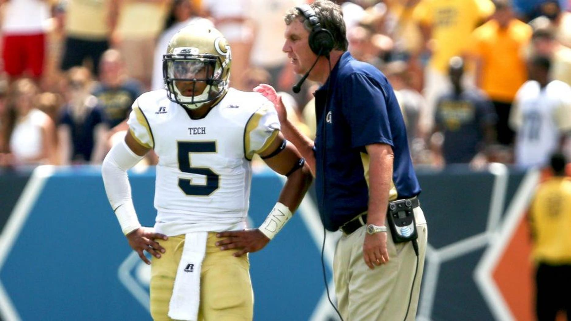 Aug 30, 2014; Atlanta, GA, USA; Georgia Tech Yellow Jackets head coach Paul Johnson talks with quarterback Justin Thomas (5) during the second quarter at Bobby Dodd Stadium. Georgia Tech won 38-19. Mandatory Credit: Kevin Liles-USA TODAY Sports