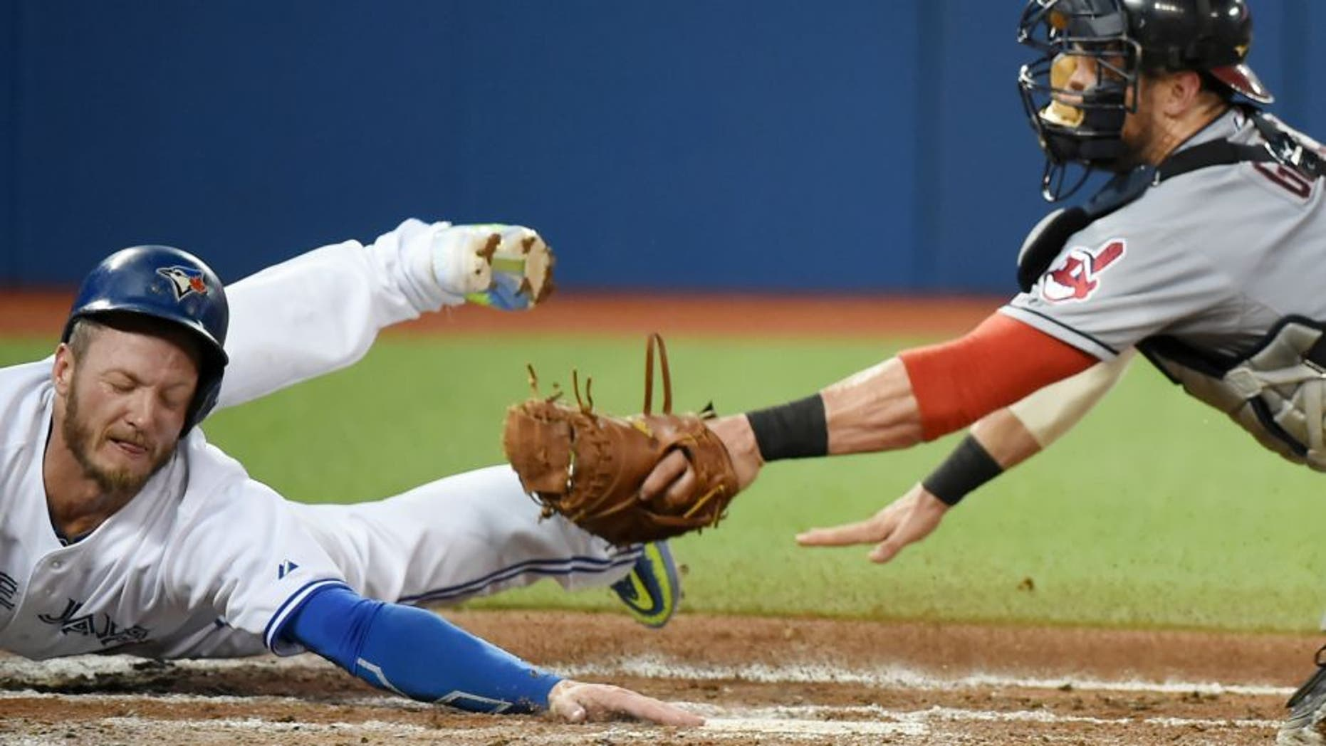 Sep 2, 2015; Toronto, Ontario, CAN; Toronto Blue Jays third baseman Josh Donaldson (20) eludes the tag of Cleveland Indians catcher Yan Gomes (10) to score in the second inning at Rogers Centre. Mandatory Credit: Dan Hamilton-USA TODAY Sports