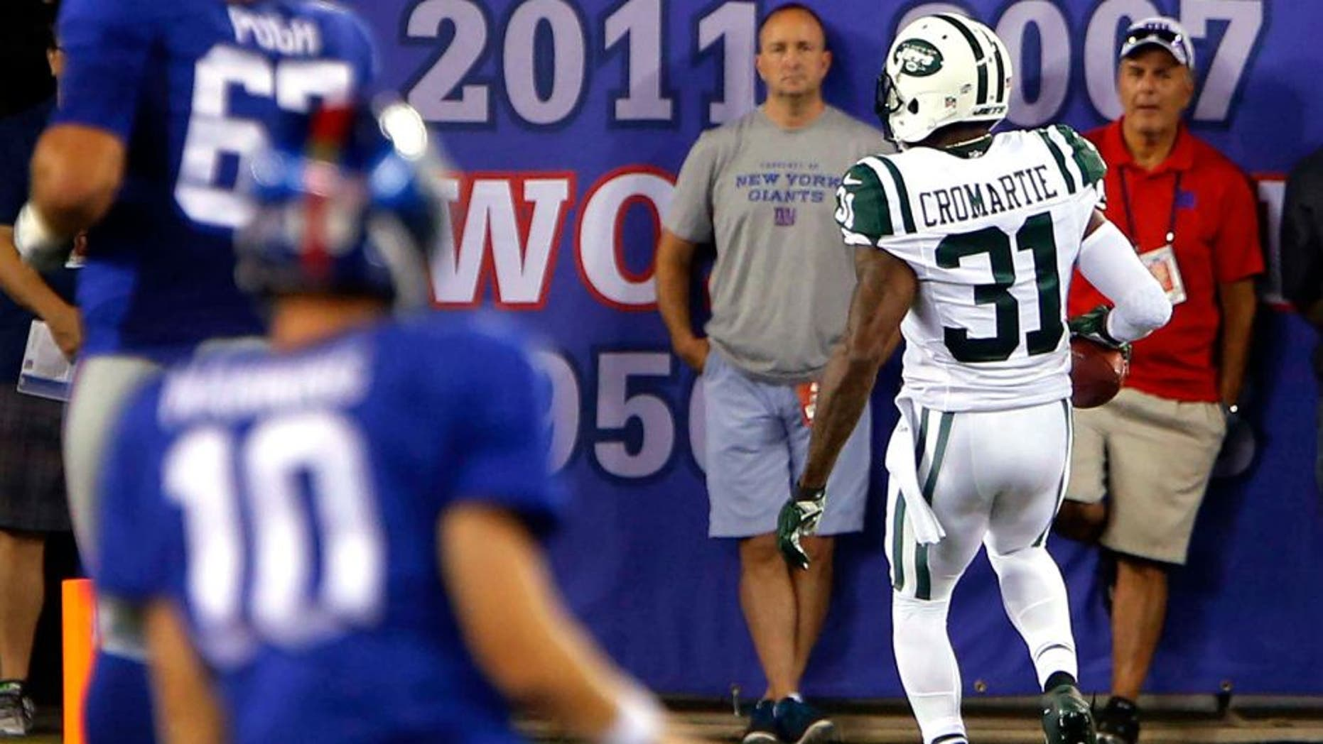 Aug 29, 2015; East Rutherford, NJ, USA; New York Giants quarterback Eli Manning (10) watches New York Jets defensive back Antonio Cromartie (31) score a touchdown after intercepting his pass during the first half at MetLife Stadium. Mandatory Credit: Noah K. Murray-USA TODAY Sports