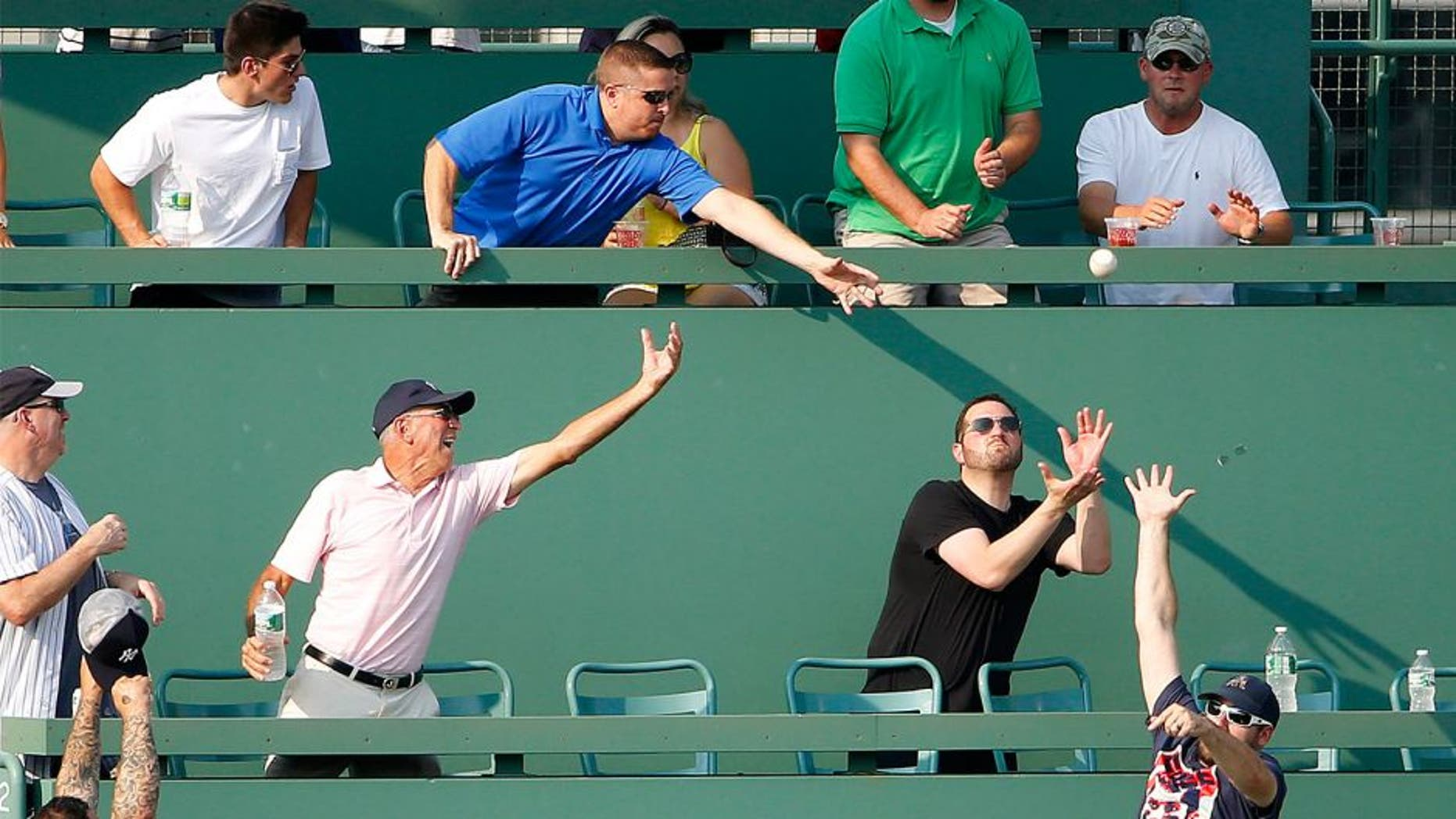 Fans in the Monster Seats go for a home run ball hit by New York Yankees' John Ryan Murphy during the second inning of a baseball game against the Boston Red Sox at Fenway Park in Boston Wednesday, Sept. 2, 2015. (AP Photo/Winslow Townson)