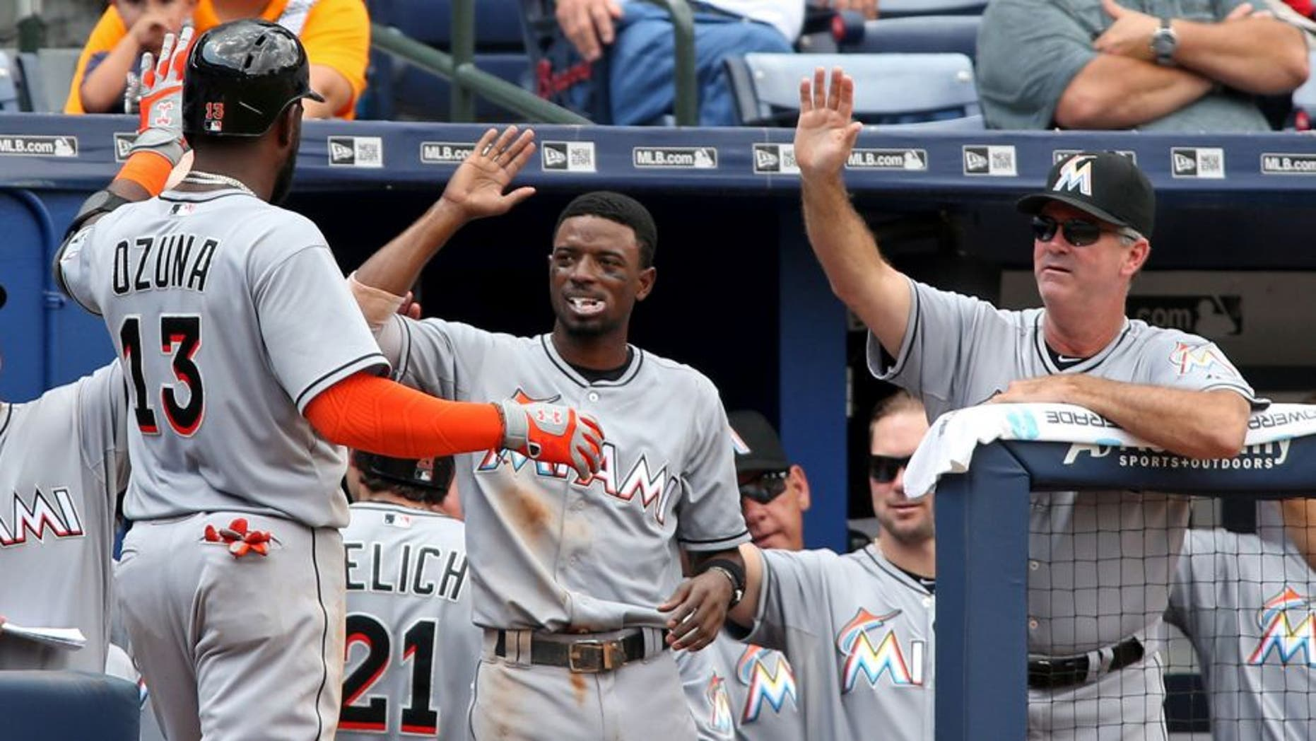 Sep 2, 2015; Atlanta, GA, USA; Miami Marlins center fielder Marcell Ozuna (13) celebrates his two-run home run with second baseman Dee Gordon (center) and manager Dan Jennings (26) in the fifth inning of their game against the Atlanta Braves at Turner Field. Mandatory Credit: Jason Getz-USA TODAY Sports
