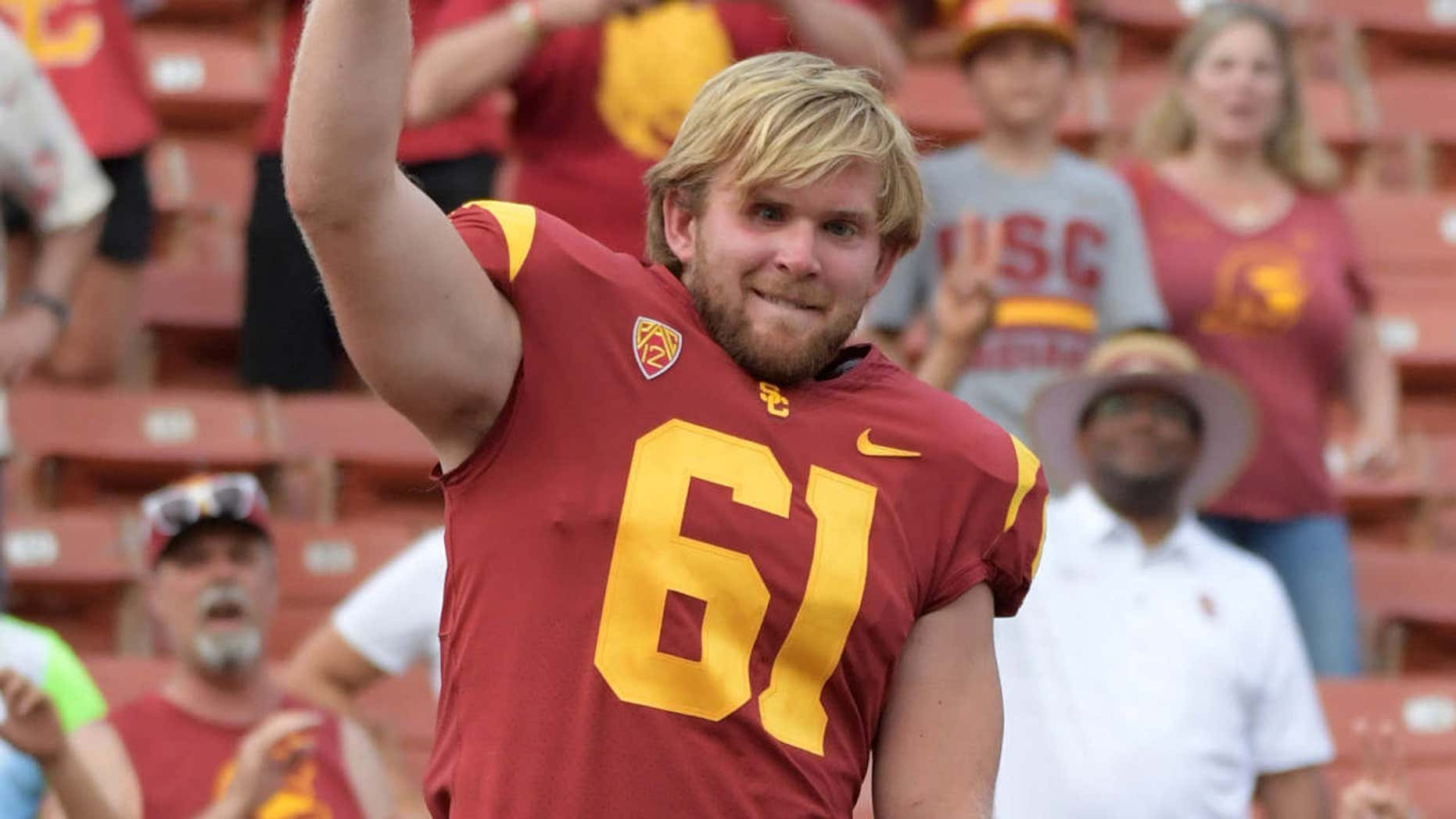 USC Trojans long snapper Jake Olson (61), who is blind, conducts the Spirit of Troy marching band after snapping the extra point in the fourth quarter against the Western Michigan Broncos during a NCAA football game at Los Angeles Memorial Coliseum.