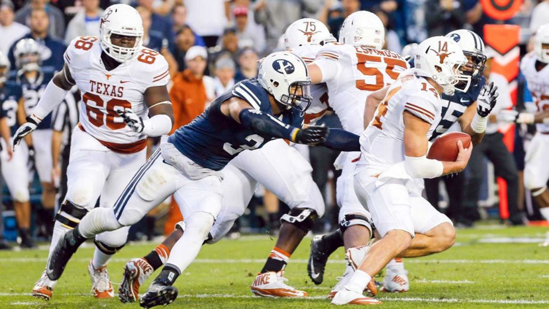 Sep 7, 2013; Provo, UT, USA; Texas Longhorns quarterback David Ash (14) tries to get away from Brigham Young Cougars linebacker Kyle Van Noy (3) during the first quarter at Lavell Edwards Stadium. Mandatory Credit: Chris Nicoll-USA TODAY Sports