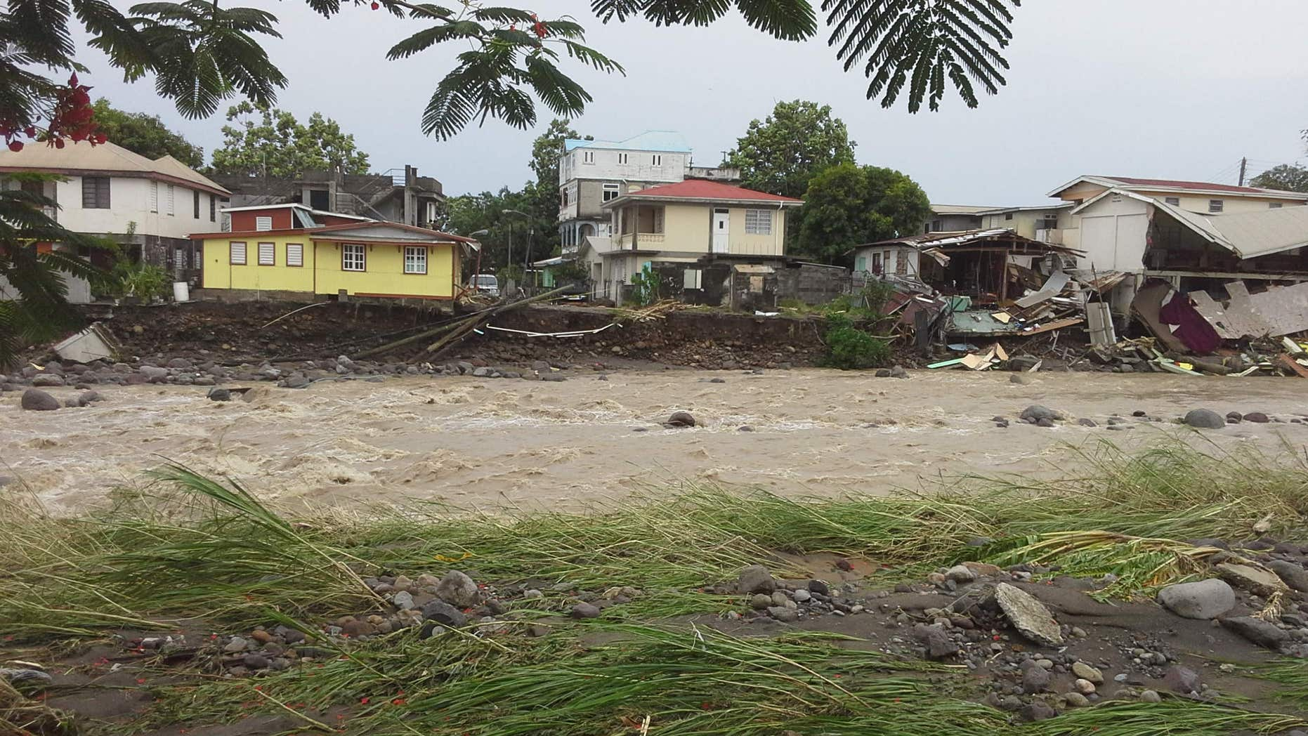 Aug. 27, 2015: A river overflows, affecting some homes along its banks, due to Tropical Storm Erika in Roseau, Dominica.