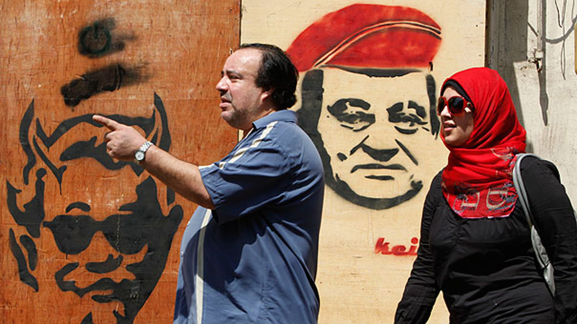 Sept. 4: Egyptians walk in front of an anti- ousted Egyptian President Hosni Mubarak graffiti in Cairo, Egypt, a day before the third trial session of him, his two sons, his former security chief and six other senior officials on charges of conspiring to kill protesters during mass uprising that ousted them from power.
