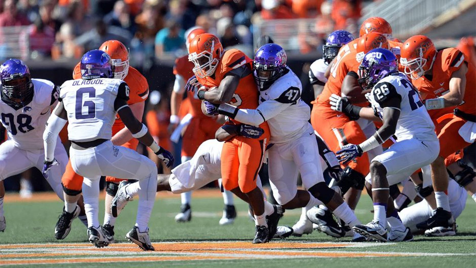 Oct 19, 2013; Stillwater, OK, USA; Texas Christian Horned Frogs linebacker Paul Dawson (47) wraps up Oklahoma State Cowboys running back Rennie Childs (23) during the second half at Boone Pickens Stadium. Oklahoma State won 24-10. Mandatory Credit: Peter G. Aiken-USA TODAY Sports