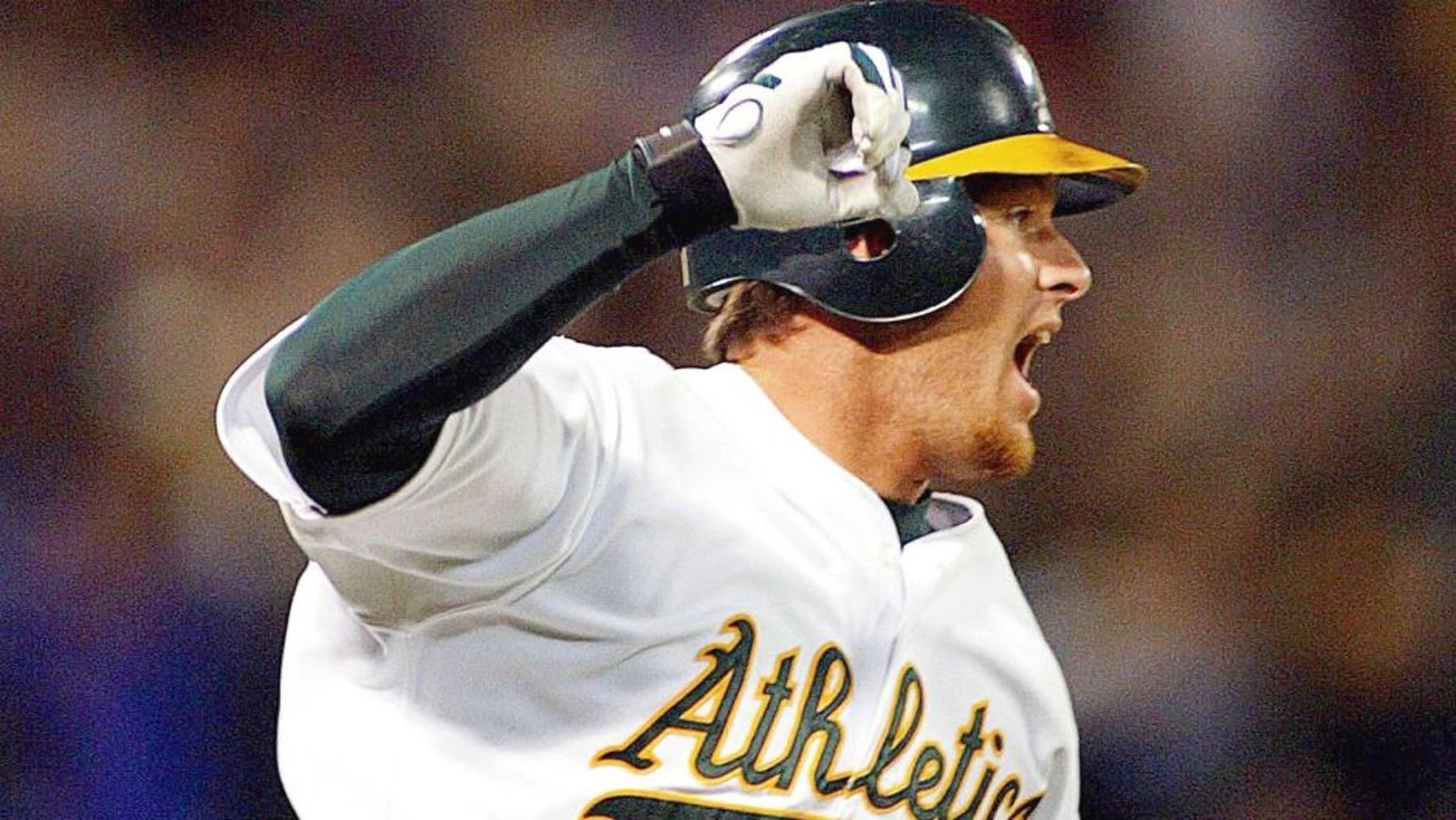 OAKLAND, UNITED STATES: Oakland Athletics' Scott Hatteberg raises his arms after hitting the game winning homerun against the Kansas City Royals 04 September 2002 during the bottom of the ninth inning off Royals' pitcher Jason Grimsley. It was the Athletics' 20th record straight win for the American League. The A's defeated the Royals 12-11. AFP PHOTO/John G. MABANGLO (Photo credit should read JOHN G. MABANGLO/AFP/Getty Images)