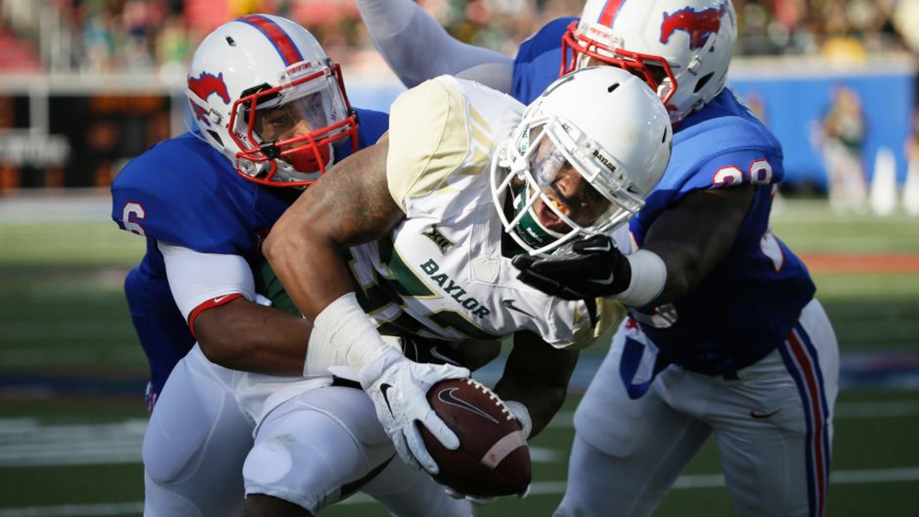 Baylor running back Shock Linwood (32) runs against SMU defenders Shakiel Randolph, right, and Jesse Montgomery (6) during the first half of an NCAA college football game Friday, Sept. 4, 2015, in Dallas. (AP Photo/LM Otero)